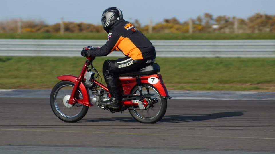 """A very silly person racing a 90cc Honda """"pizza bike"""" on a circuit in Anglesey in Wales"""