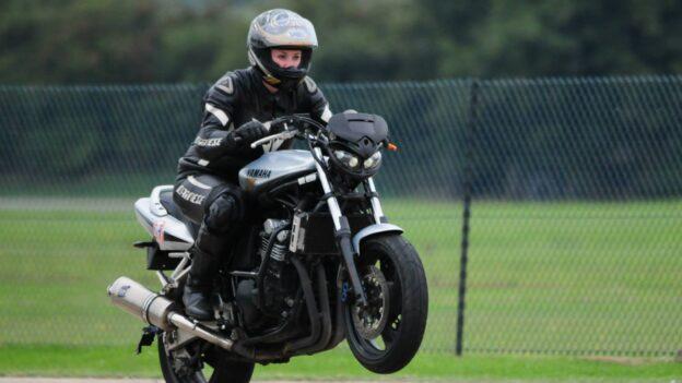 Zoë doing a wheelie on somebody else's motorbike
